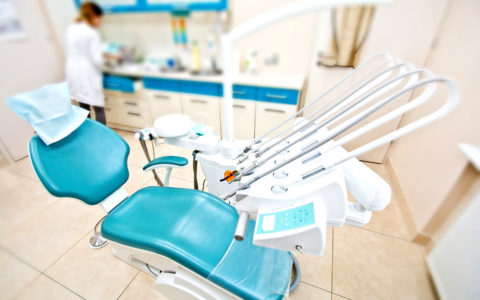 Professional Dentist tools and chair in the dental office. Dental Hygiene and Health conceptual image.